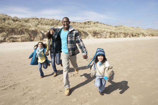 Family Running On Winter Beach