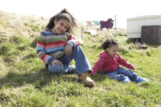 Young Girls Sitting Outside In Caravan Park