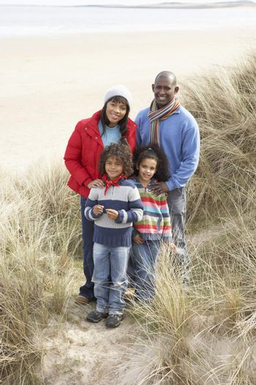 Family Walking In Dunes On Winter Beach