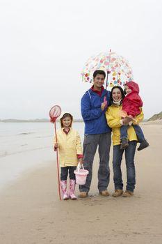 Happy family on beach with umbrella
