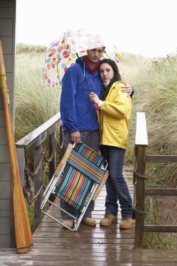 Young couple on beach with umbrella