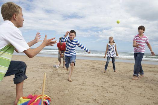 Teenagers playing baseball on beach