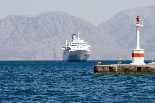 Tourist white cruise sea liner sails to lightship in rocky bay on the islands background
