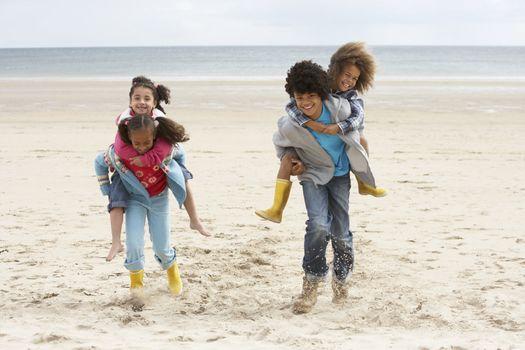 Happy children playing piggyback on beach