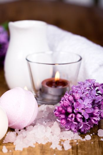 spa products (towel, salt, candles, flower, balls) on wooden background