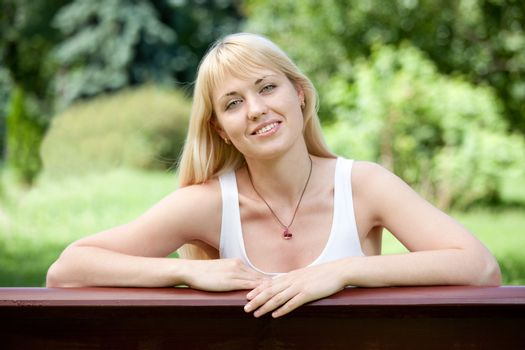 Young Smiling optimistic cheerful blond girl 20-29 sits on the bench in summer park