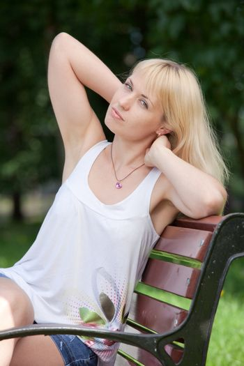 Calm balanced pretty blond girl 20-29 with raised hands and long hair is sitting on the park bench in summer