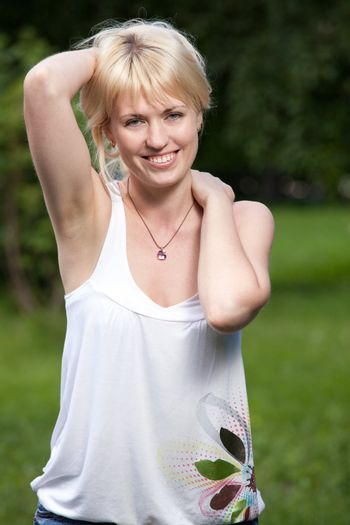 Smiling cheerful blond girl 20-29 with raised hands and long hair is walking in summer park