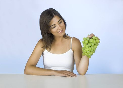 Beautiful young woman holding grapes on her hands
