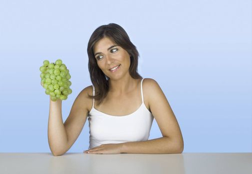 Beautiful young woman holding and looking to the grapes