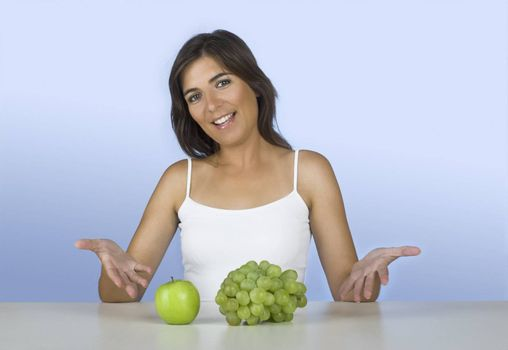Beautiful young woman showing grapes and apples