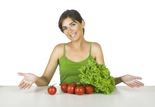 Beautiful young woman in the kitchen with healthy vegetables in front of her