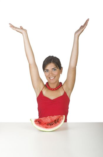 Beautiful young woman in the kitchen with both arms on the air and with a watemelon slice in front of her