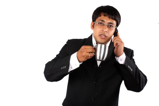 An Indian businessman talking on the cellphone during the coffee break, on white studio background.