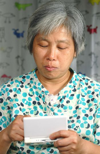 chinese woman playing handheld game console