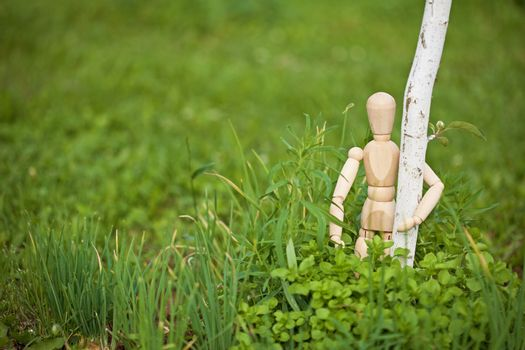 Toy man embraces young tree