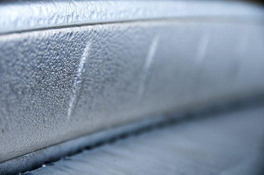 Closeup of droplets on a metallic car bumper