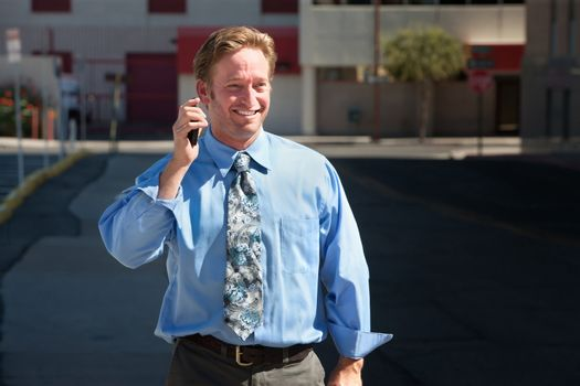 Pleased, good-looking guy talks on cell phone.