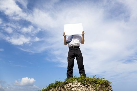 Businessman standing on a peak and holding blank billboard