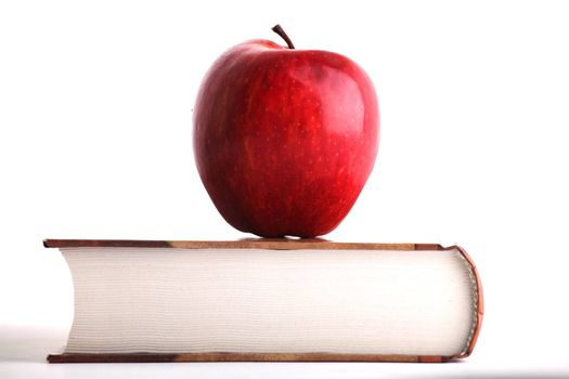 Red apple on the big book on white background