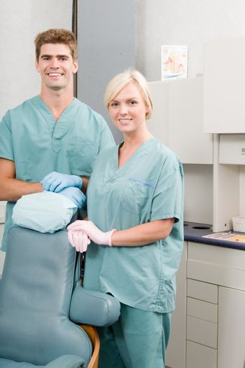 A happy dentist and assistant standing in a dental clinic