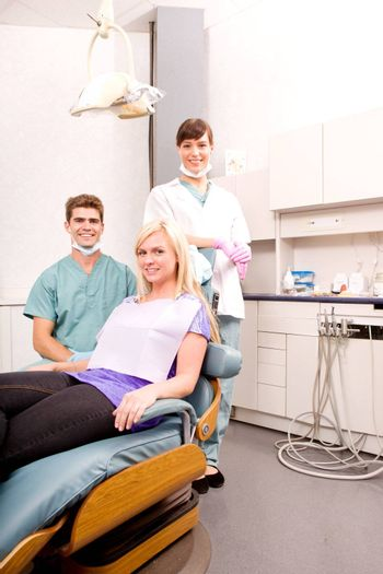 A dental clinic with dentist, assistant and patient