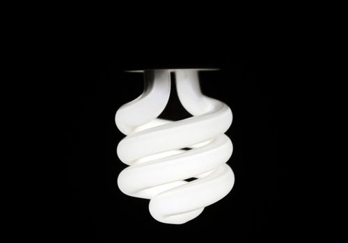 Glowing compact fluorescent bulb hanging upside down against a dark background