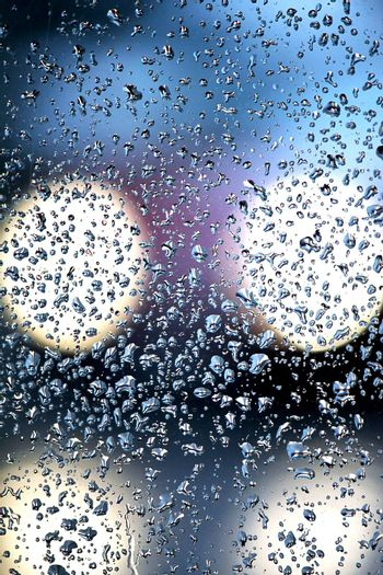 View of a glass with many droplets of water lit by a passing car.
