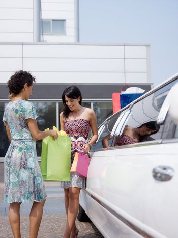 two women standing by limousine and looking at shopping bags. Vertical shape, copy space