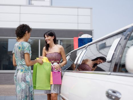 two women standing by limousine and looking at shopping bags. Horizontal shape, copy space