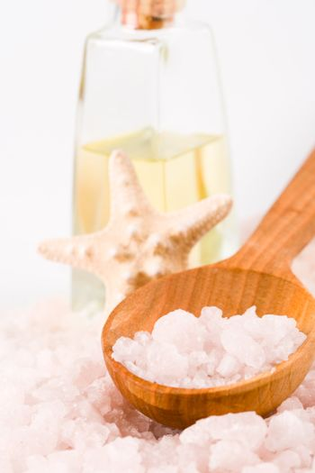 spa products: sea salt on wooden spoon, towel, oil and stars