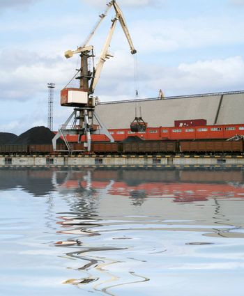 Container cranes for loading and unloading freight trains in Latvian port. Reflection over water.