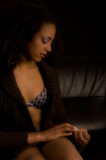 African woman in lingerie is resting on the coach