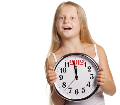 The girl hold in hands a big clock with figures 2012. It is isolated on a white background