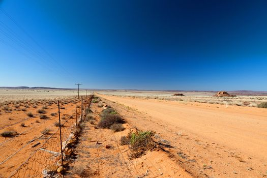 Road through a vast, arid landscape - horizontal