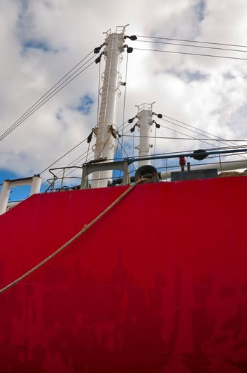 Hull and masts of a red old freighter with pulleys