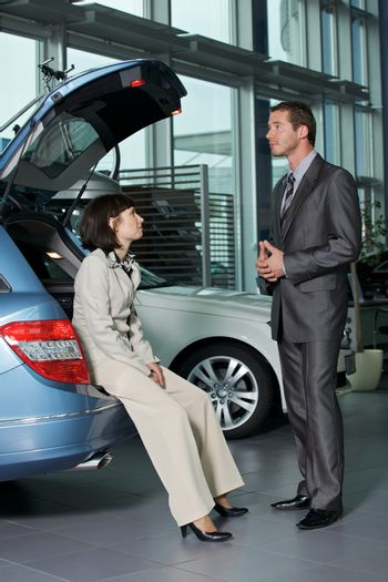 Car sales person talking with customer