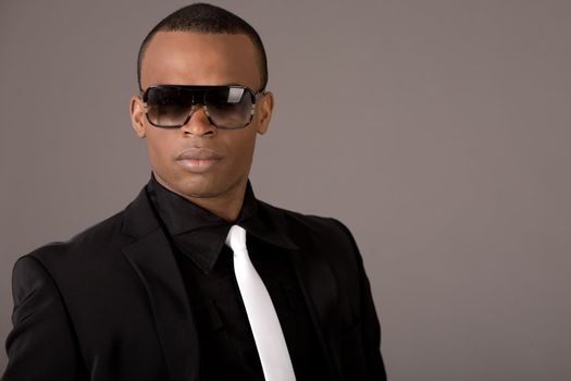 Ethnic young business man wearing sunglasses indoor studio