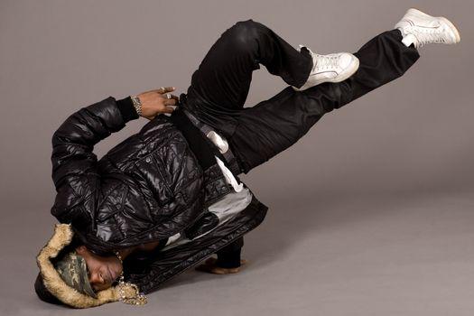 Portrait of hip hop dancer in head stand on grey background