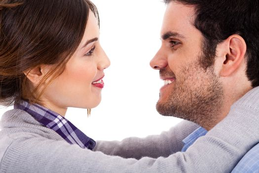 Beautiful couple smiling and facing each other on a isolated white background