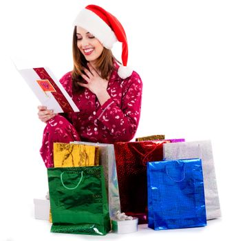 young lady reading christmas greeting card with gift bags around her