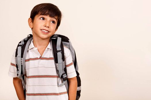 Portrait of young schoolboy with back pack looking left cornor, isolated on ivory background