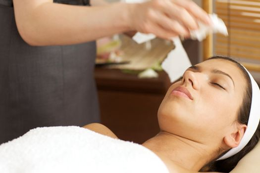 Masseuse cleaning face of young woman with tissue paper