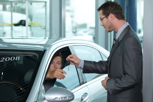Man getting keys to new car through salesperson