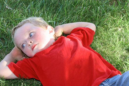 Little boy in red laying in the shady grass with hands behind head deep in thought