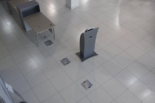 Interior of shop, grey tiled floor, grey rack, grey furniture, the top view