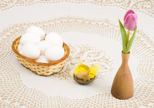 a basket of eggs, easter chicken and a pink tulip