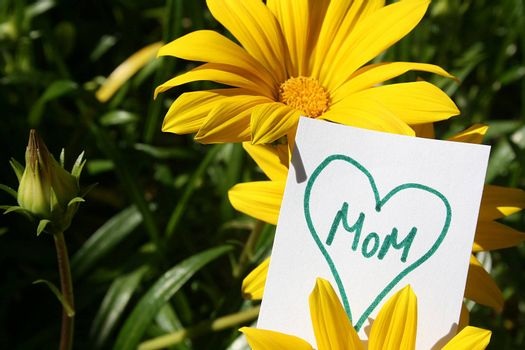 Flowers with a heart with the word Mom in it on a white paper sign.