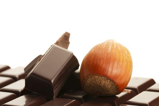 hazelnut and chocolate pieces on a plain chocolate bar