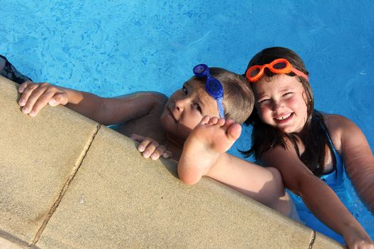 brother and sister with diving glasses in the swimmingpool